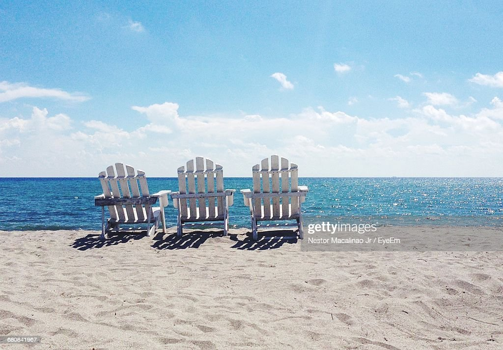 Empty Adirondack Chair On Sand At Beach Against Sky