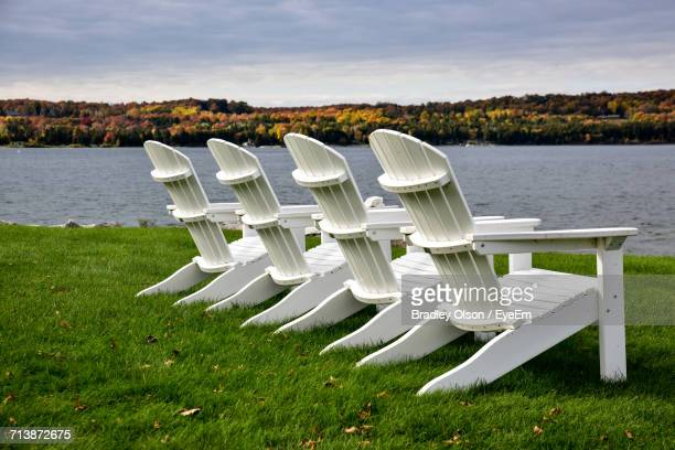 Empty Adirondack Chairs At Grassy Lakeshore Against Cloudy Sky
