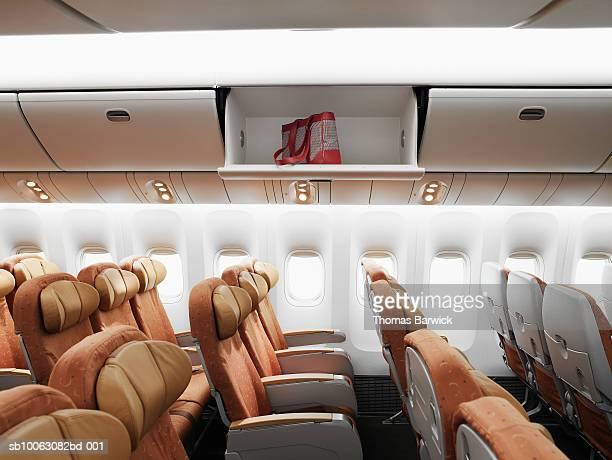 Empty airplane interior, bag left in overhead bin, side view