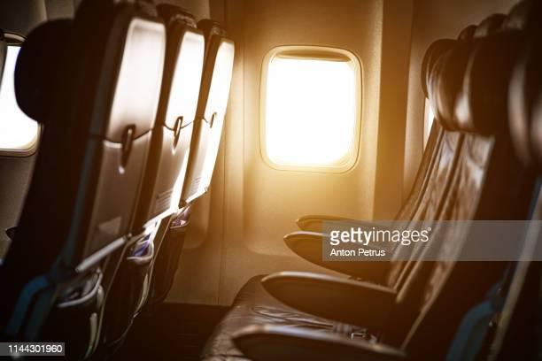 empty airplane seats in the cabin in sunset light - voertuiginterieur stockfoto's en -beelden