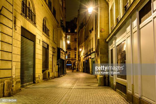 empty alley along buildings at night - paris night stock pictures, royalty-free photos & images