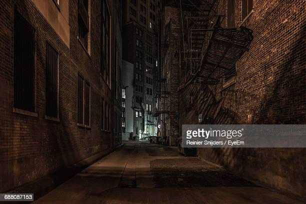 Empty Alley Amidst Buildings At Night