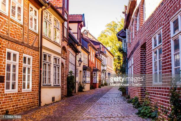 empty alley amidst buildings in city - lüneburg stock pictures, royalty-free photos & images