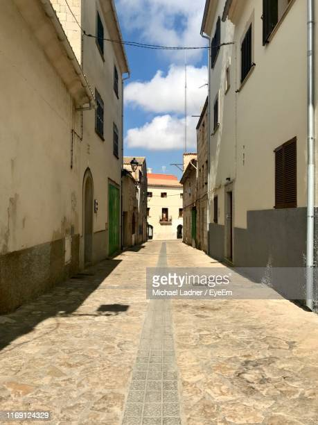 empty alley amidst buildings in city - muro stock photos and pictures