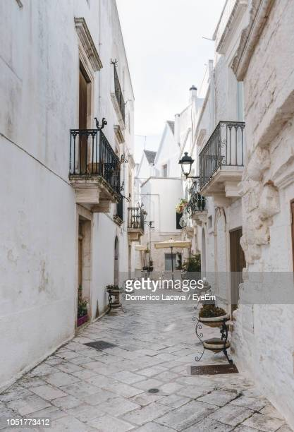 empty alley amidst buildings in town - locorotondo stock photos and pictures