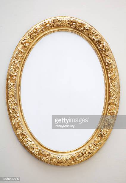Empty Antique Mirror in Gilt Oval Frame on Neutral Wall