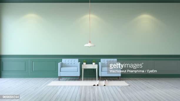 empty armchairs against green wall - pendant light stock pictures, royalty-free photos & images