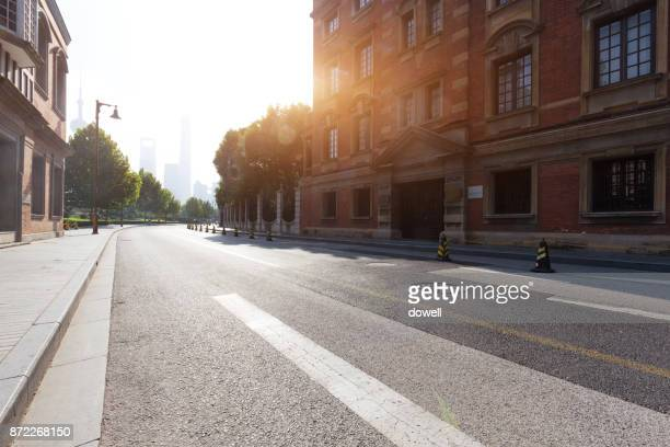 empty asphalt city road with sunbeam - stadtzentrum stock-fotos und bilder