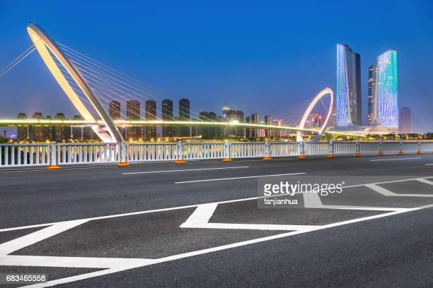 empty asphalt highway through modern city