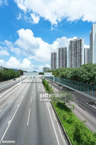 empty asphalt road by residential apartments - freie straße stock-fotos und bilder