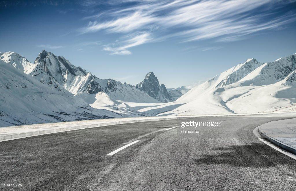 empty asphalt road leading towards snow mountains : Stock Photo