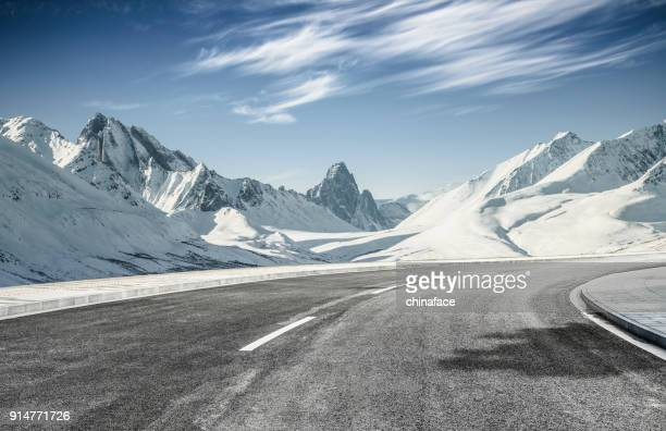 empty asphalt road leading towards snow mountains - strada foto e immagini stock