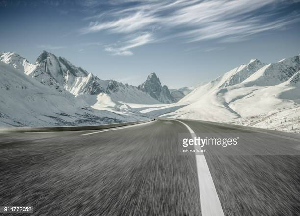 empty asphalt road towards snow mountains,blurred motion