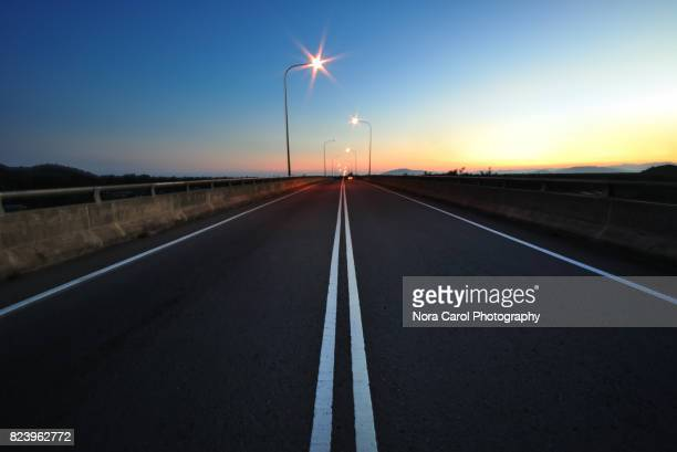 empty asphalt road with lamp post during sunrise - mid section stock photos and pictures