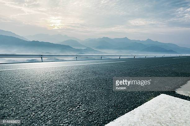 empty asphalt road with mountain mist in the back - grand angle photos et images de collection