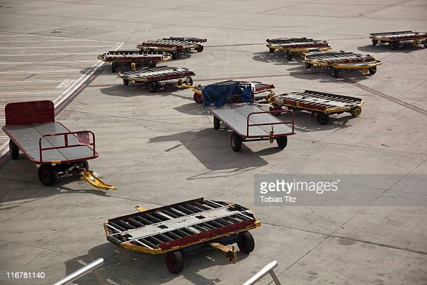 Empty baggage trailers on an airport tarmac