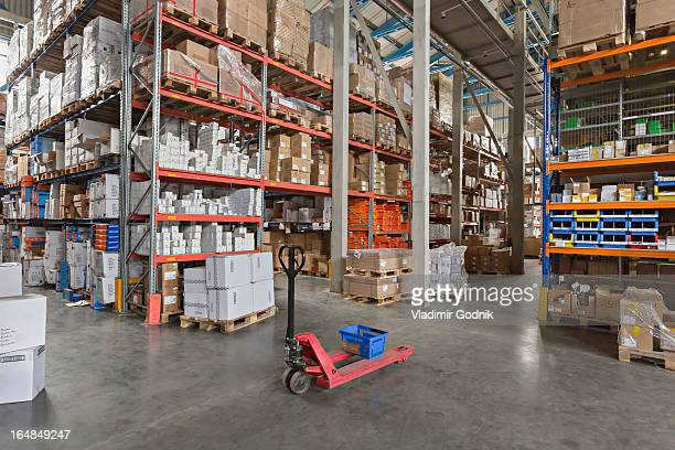 Empty basket on hand pallet truck in large warehouse