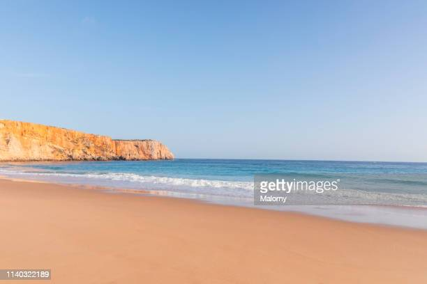 empty beach and wavy sea. rocks and coastline in the background. - praia imagens e fotografias de stock
