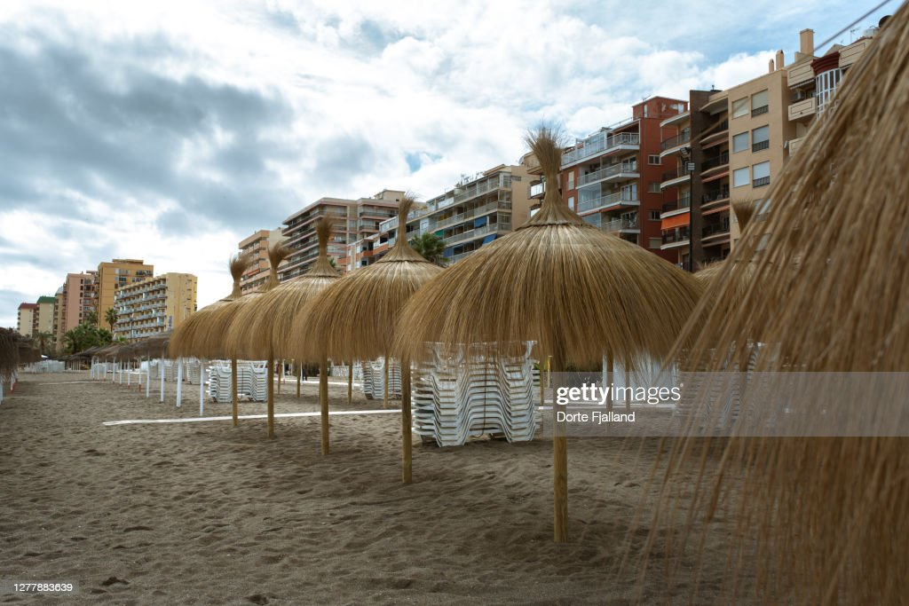 Empty beach with a line of sun umbrellas and apartment buildings in the back : Foto de stock