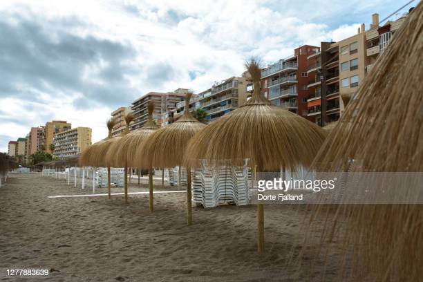 empty beach with a line of sun umbrellas and apartment buildings in the back - dorte fjalland fotografías e imágenes de stock
