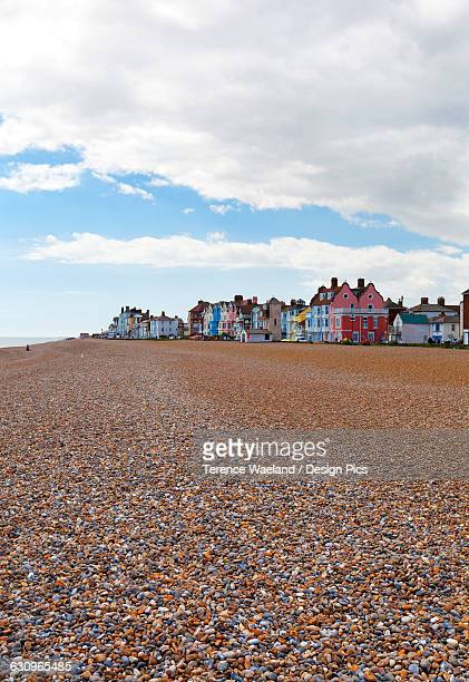 empty beach with colourful resort houses in the distance - east anglia stock pictures, royalty-free photos & images