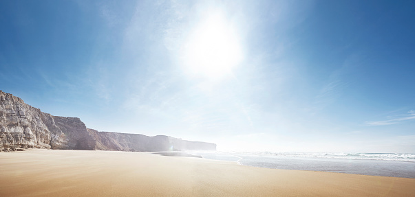 Empty beach with sun and distant cliffs panoramic - gettyimageskorea