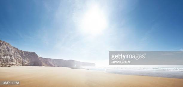 empty beach with sun and distant cliffs panoramic - sunny stock pictures, royalty-free photos & images
