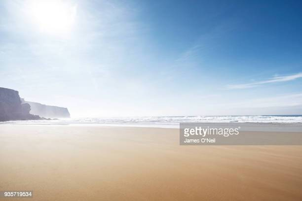 empty beach with sun and distant cliffs - sagres stock pictures, royalty-free photos & images