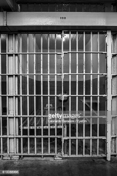 Empty Bed In Illuminated Prison Cell