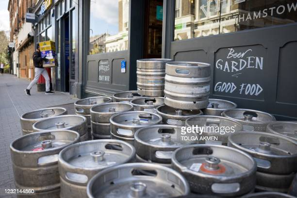 Empty beer barrels wait to be collected outside The Village Pub in Walthamstow, northeast London on April 6 as it restocks ahead of partial...