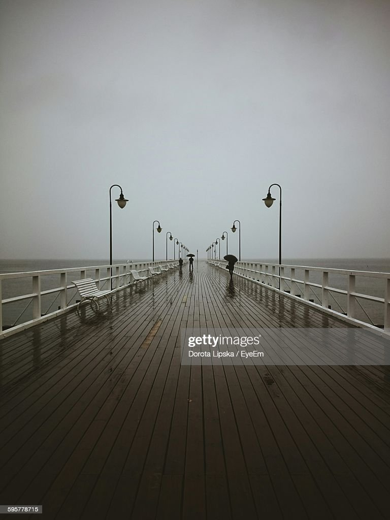 Empty Bench And Street Lights On Pier Over Sea Against Clear