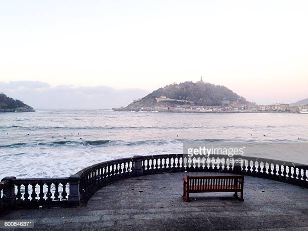 Empty Bench At Promenade By Sea Against Sky