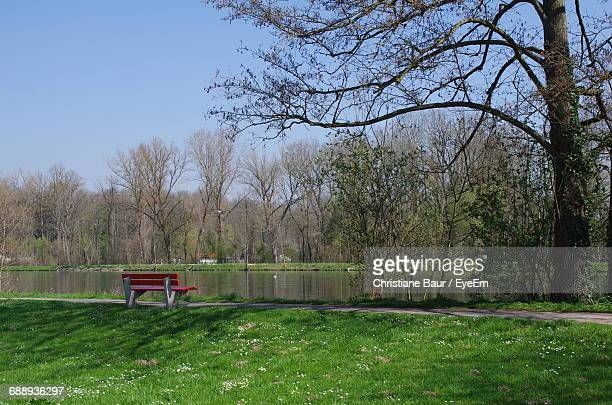 Empty Bench By Footpath At Riverbank Against Sky