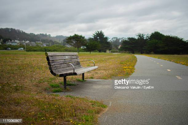 empty bench by road against sky - oleksandr vakulin stock pictures, royalty-free photos & images