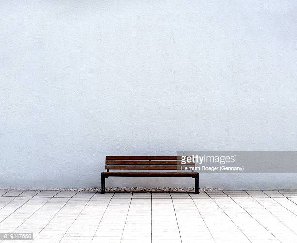 empty bench in front of a white wall - bench stock pictures, royalty-free photos & images