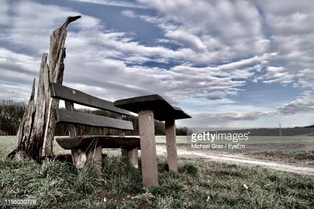 empty bench on field against sky - gras stock pictures, royalty-free photos & images