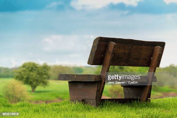 empty bench on field against sky - jens siewert stock-fotos und bilder