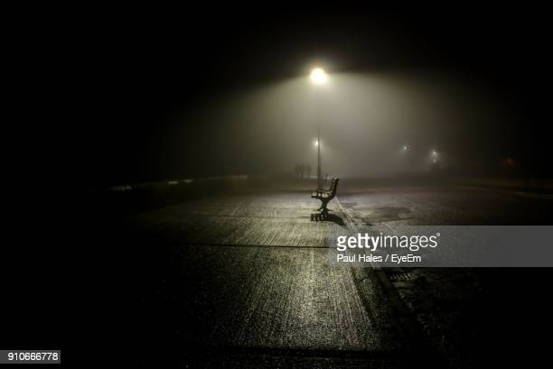empty bench on illuminated sidewalk by street at night - low stock photos and pictures