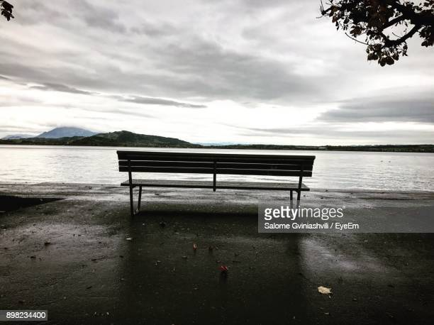 Empty Bench On Shore Against Sky