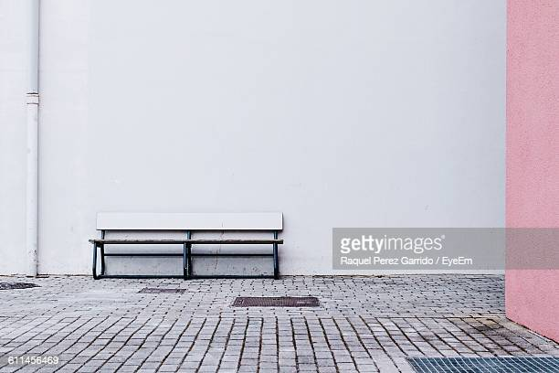 empty bench on sidewalk against white wall - bench stock pictures, royalty-free photos & images