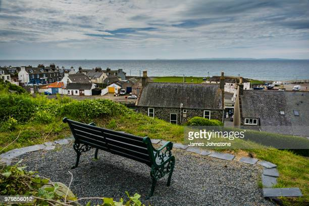 empty bench overlooking fishing village and port william, dumfries and galloway, scotland, uk - galloway scotland stock pictures, royalty-free photos & images