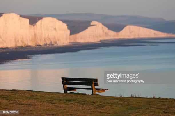 Empty bench with coastline