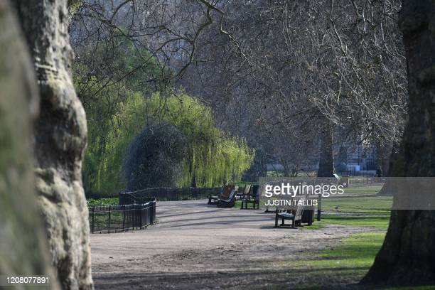 Empty benches are seen in Green Park in central London on March 24 2020 after Britain ordered a lockdown to slow the spread of the novel coronavirus...