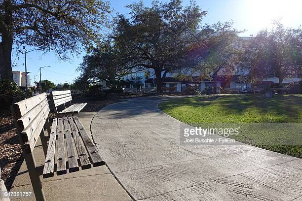 empty benches by footpath in park against trees - coral gables stock pictures, royalty-free photos & images