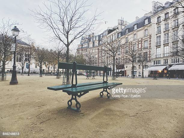 Empty Benches In Park Against Buildings In City