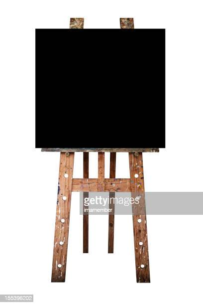 Empty black artist canvas on easel, isolated on white background