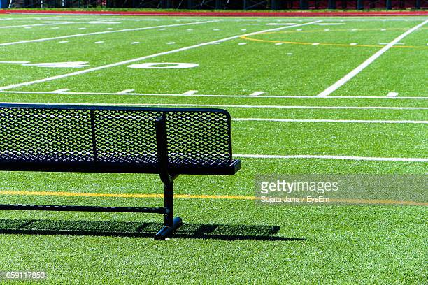 empty black bench on soccer field during sunny day - forty yard line stock pictures, royalty-free photos & images