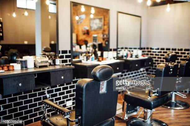 empty black chairs and mirrors in barber shop - barber shop stock photos and pictures