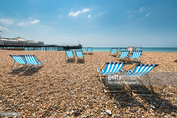 empty blue and white striped deck chairs on brighton beach - heatwave stock pictures, royalty-free photos & images