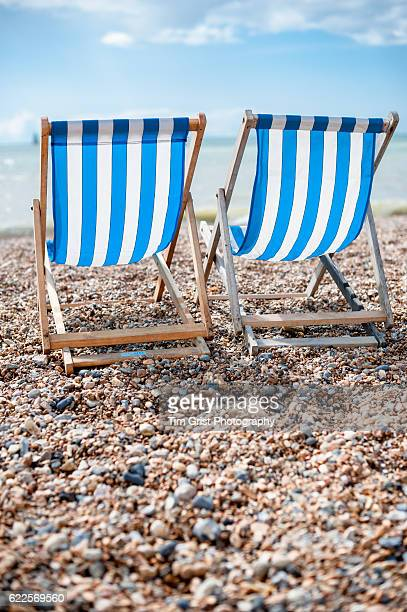 Empty Blue and White Striped Deck Chairs